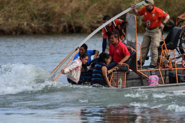 Agents from Mexico's Beta group rescue Central American migrants from the Rio Grande River between Piedras Negras, Mexico, and Eagle Pass, Texas, on February 15. Photo by Miguel Sierra/EPA-EFE