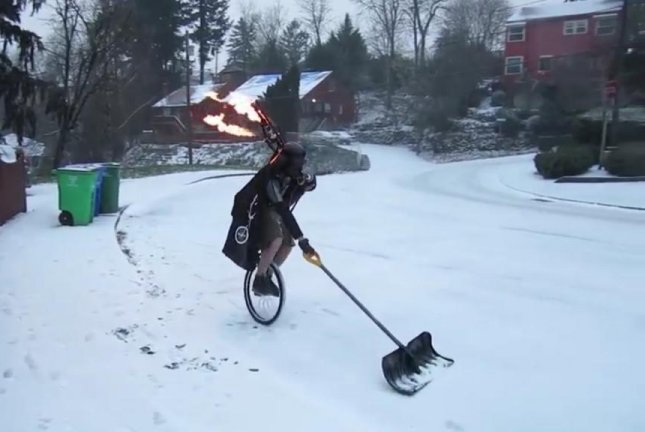 Portland's Unipiper shovels snow while riding a unicycle, playing flame-shooting bagpipes, and wearing a Darth Vader costume. Screenshot: Storyful