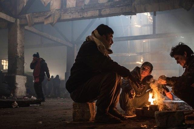 To fend off the cold, migrants living in an abandoned train depot in Belgrade light indoor campfires, which fill the buildings with thick smoke. Photo by Diego Cupolo/Refugees Deeply