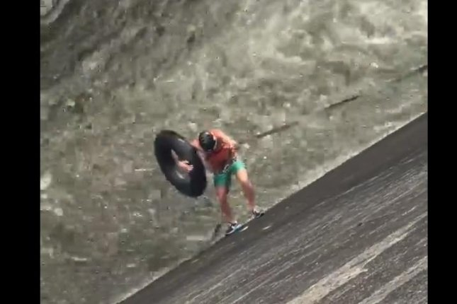 A daredevil rappels down the wall of a New Zealand dam to ride the rapids in an inner tube. Screenshot: West Auckland Updates/Facebook