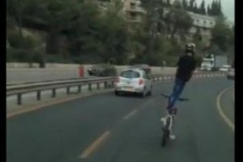 A daredevil cyclist on a busy stretch of Israeli highway performs tricks in traffic. Rumble video screenshot