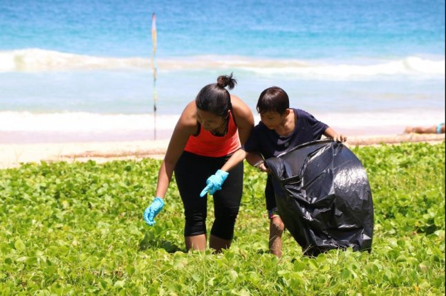 Beach cleanup participants team up to gather plastic and other waste from a waterfront area in Thailand. Photo by Eric Cirino