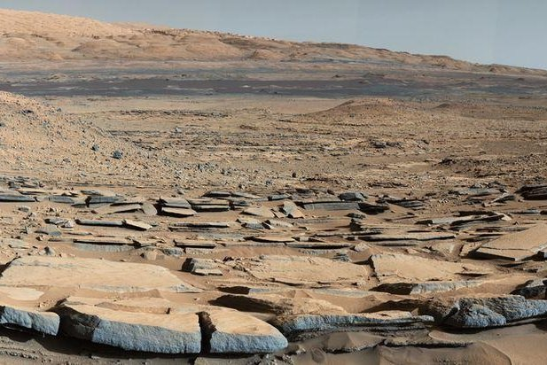 A view from the Kimberley formation on Mars taken by NASA's Curiosity rover. The strata in the foreground dip towards the base of Mount Sharp, indicating flow of water toward a basin that existed before the larger bulk of the mountain formed. Photo by NASA / JPL-Caltech / MSSS