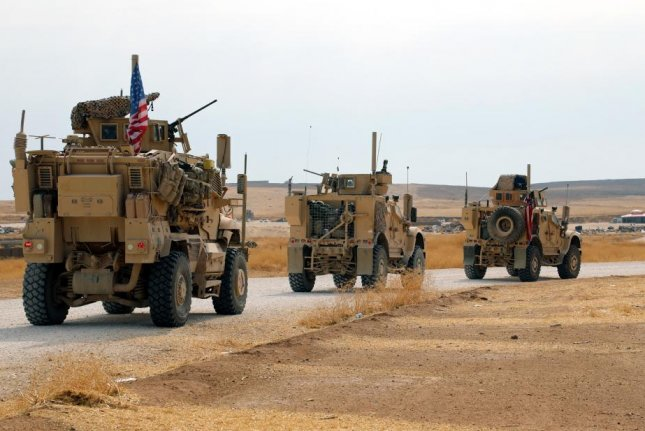 A convoy of U.S. troops head toward the Iraqi borders in northeastern Syria Sunday. Photo by Ahmed Mardnli/EPA-EFE