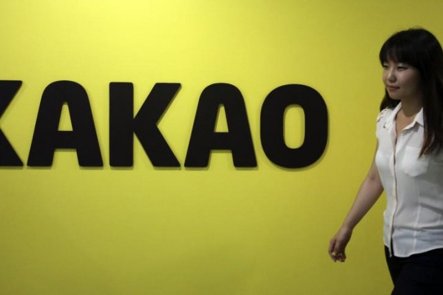 A woman passes by a logo sign in front of the headquarters of Kakao Corp., South Korea's leading mobile messenger service, in Seongnam City, Gyeonggi Province, South Korea. File photo by Yonhap/EPA