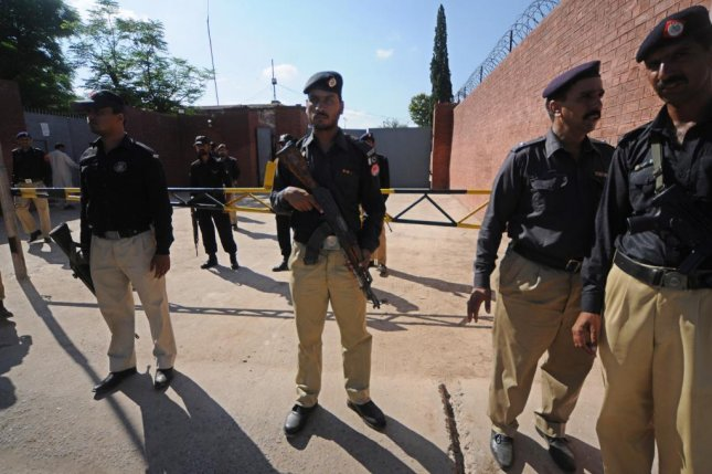 Security officers stand patrol outside the courthouse in Pakistan Thursday after verdicts were announced in the assassination of former Prime Minister Benazir Bhutto. Photo by S. Shazad/EPA