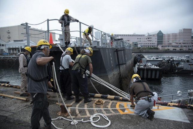 Sailors and civilian members of U.S. Fleet Activities Yokosuka Port Operations and Ship Repair Facility and Japan Regional Maintenance Center assist Japanese Maritime Self-Defense Force auxiliary, multi-purpose support ship Enshu during a dry dock evolution for scheduled maintenance in this July photo. Photo by Ryo Isobe/U.S. Navy
