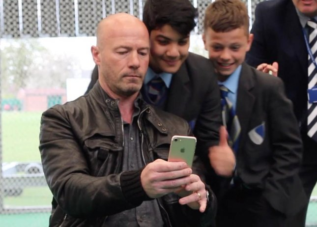 Former England soccer star Alan Shearer broke the Guinness World Record for most self-portrait photographs (selfies) taken in 3 minutes by posing for 134 photos with students from the Newcastle School for Boys.  Screen capture/Guinness World Records/YouTube