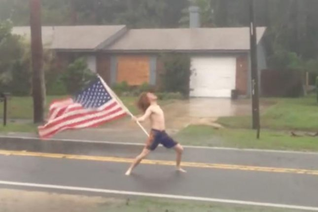 A Florida man stood in the streets in front of his house while carrying an American flag and playing Slayer's Raining Blood during Hurricane Matthew.  Screen capture/Lane Pittman/Facebook