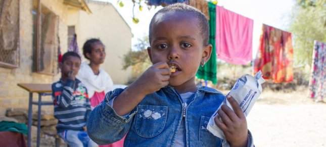 A 3-year-old girl in western Tigray eats a high energy biscuit to boost her nutrition levels. Photo by Esiey Leul Kinfu/UNICEF