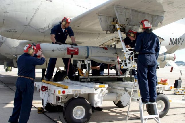 U.S. Navy aviation ordnancemen load a SLAM-ER missile onto an aircraft. Photo by Photographers Mate 3C Shannon R. smith/U.S. Navy
