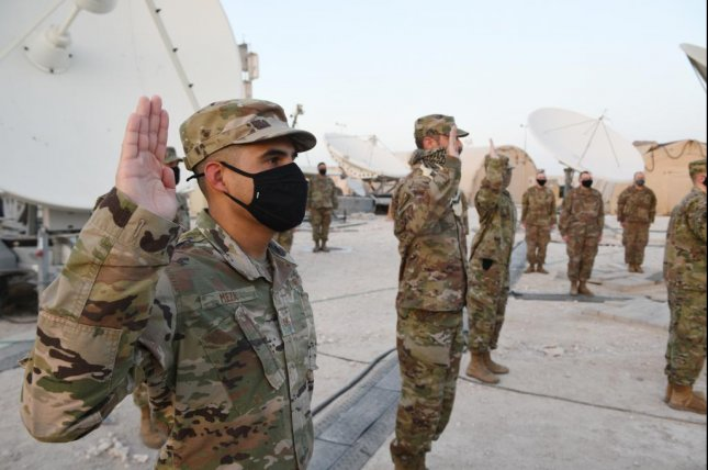 Airmen deployed to Al Udeid Air Base, Qatar, raise their right hands during an enlistment ceremony as they transferred into the Space Force Monday. Photo by Kayla White/U.S. Air Force