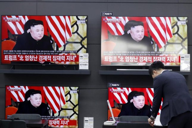 A South Korean at Yongsan electronics market in Seoul stands by a television news broadcast of U.S. President Donald Trump and North Korean leader Kim Jong Un meeting in Hanoi on Thursday. File Photo by Jeon Heon-kyun/EPA
