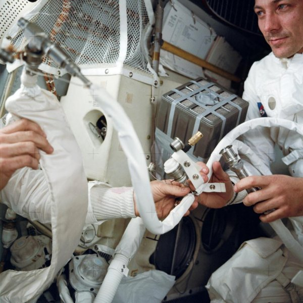Astronaut John L. Swigert, at right, with the mailbox rig improvised to adapt the Command Module's square carbon dioxide scrubber cartridges to fit the Lunar Module, which took a round cartridge. NASA Photo
