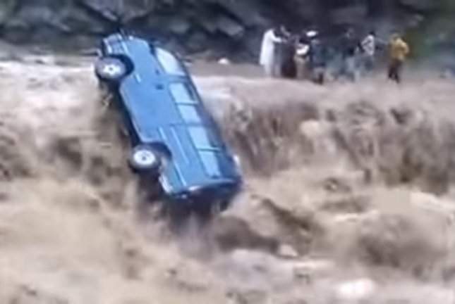 A mini bus gets stuck on a waterfall created by the rapids of a flash flood in Pakistan. Joseph Martin/YouTube video screenshot