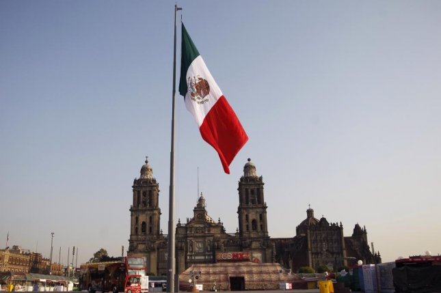 The Mexican flag is hoisted in the capital's Zocalo on February 24. Since September, 113 Mexican politicians have been killed. File Photo by Sashenka Gutierrez/EPA-EFE