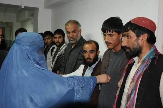 An Afghan woman tugs at one of her accused rapists' shirt. (Kabul Police)