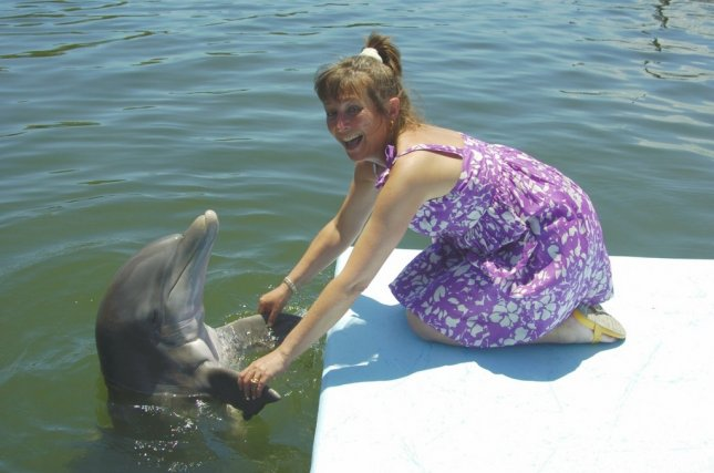 GRASSY KEY, Fla. (UPI) -- Visitor at the Dolphin Research Center in Grassy Key, Fla., shows delight with her flipper-shake with Jax, an injured rescue dolphin from Jacksonville. DRC photo. (MHP060809)