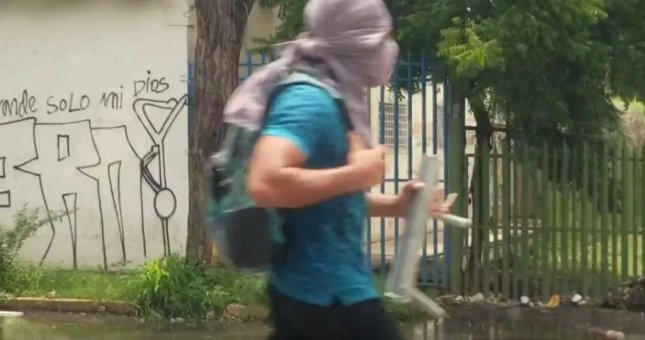 A demonstrator in Managua, Nicaragua on Monday runs toward an attack on a pro-government radio station. Photo by Ray Downs/UPI