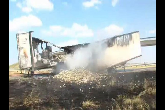 The semi truck that caught fire on Interstate 40 outside Bushland, Texas, smolders while surrounded by its spilled onions. KFDA-TV video screenshot