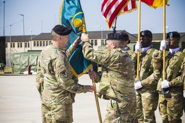 An outgoing commander, Army Field Support Battalion-Mannheim, passes the battalion colors to Col. Grant L. Morris, 405th AFSB commander, at a change of command ceremony, at Coleman Worksite in Mannheim, Germany, in July. AECOM has received a $17 million contract for support and maintenance at Mannheim and Dulmen in Germany. Photo by Rabia Coombs/U.S. Army