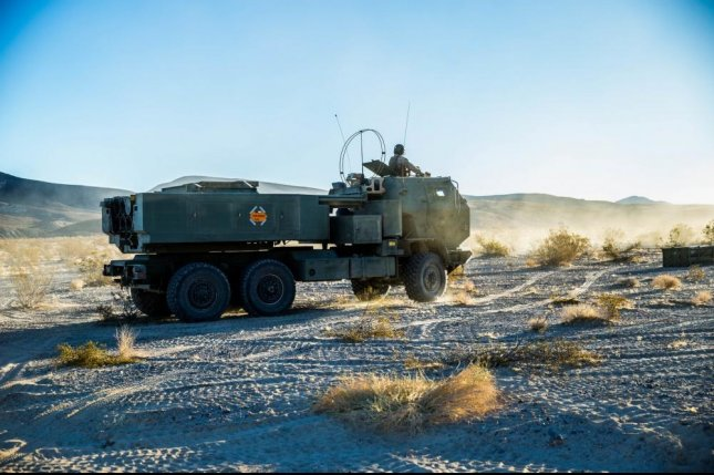 Marines head to the firing point to launch the High Mobility Artillery Rocket System from a guided multiple-launch rocket system during in Twentynine Palms, Calif., in December. Photo by Pfc. William Chockey/U.S. Marine Corps