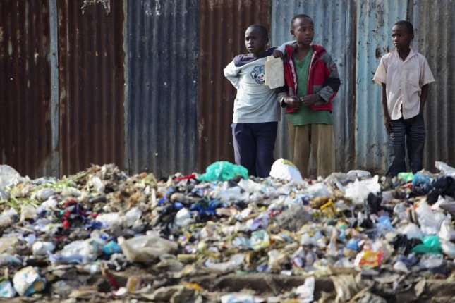Young boys stand next to a pile of rubbish including plastic bags in Mathare slum in Nairobi, Kenya. A ban on plastic bags came into effect in Kenya on Monday, making the manufacturing, selling or using of them illegal. Photo by Dai Kurokawa/EPA