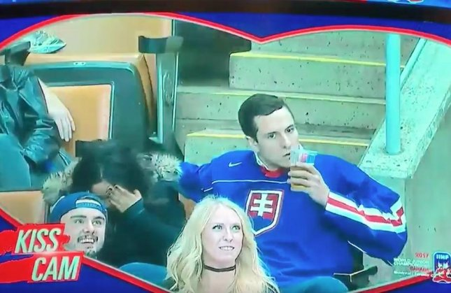The man dressed in the Slovakia hockey jersey turned away from his embarrassed date to plant a kiss on his beer cup before chugging its contents. Screen capture/Rob Williams/Twitter