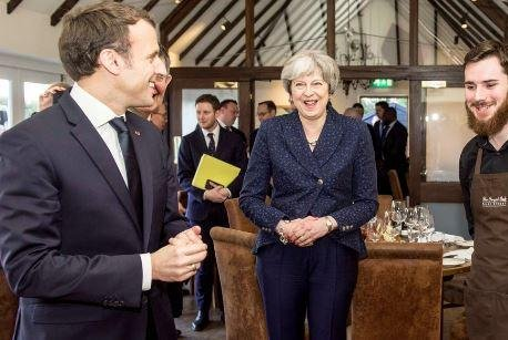 French President Emmanuel Macron ( L) and British Prime Minister Theresa May (C) meet with employees at Britain's Royal Military Academy Sandhurst on Thursday. The summit between May and Macron produced commitments to enhance defense cooperation between Britain and France. Image courtesy of Theresa May/Twitter