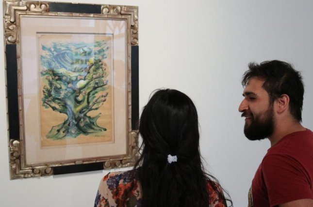 Lois Rodriguez (L) and Diego Moncayo view a painting by Mexican muralist David Alfaro Siqueiros at Interpretaciones Formales, an exhibition of artwork seized from the homes of former Veracruz Gov. Javier Duarte, who has been jailed awaiting trial. Photo courtesy of Tim MacFarlan