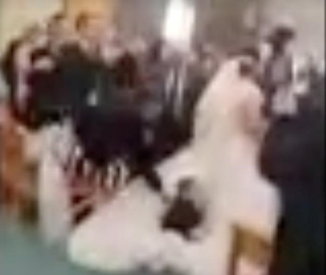 Young Boy Dives Onto Bride's Dress During Wedding Ceremony
