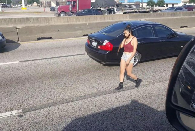 A young woman on her cellphone walks between two lanes on I-45 in Houston. Screenshot: Jefe De Jefes/Facebook