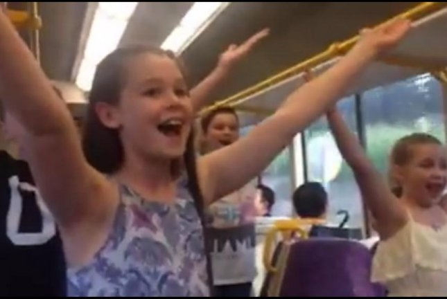 Young cast members from a production of The Sound of Music perform for commuters on a Brisbane, Australia, train. Screenshot: Allport Millinery/Facebook video