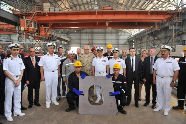 Egyptian navy officers and officials of DCNS and Alexandria Shipyard display steel cut for a naval corvette. Photo courtesy DCNS