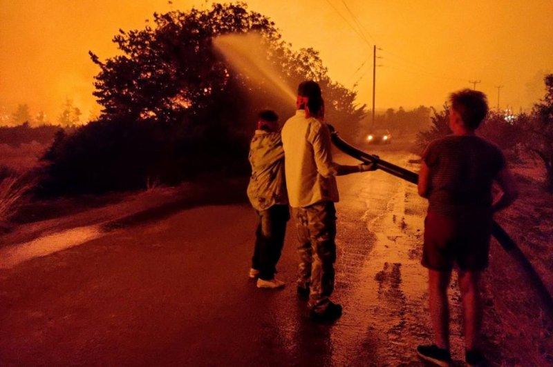 Residents fight a wildfire on the island of Evia island along the eastern Greek coast on Wednesday. Photo by Panagiotis Kouros/EPA-EFE