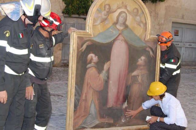 Firefighters help save artwork from the church of San Lorenzo Martire after an earthquake in Norcia in central Italy on November 1. A 17th century oil painting was stolen from a church in the village of Nottoria, which is near Norcia. Photo by Italian Fire Department/European News Agency