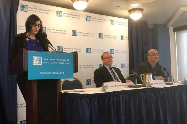 Tamara Kharroub, assistant director at the Arab Center in Washington, DC, releases findings from a 2016 opinion index survey conducted in the Middle East, as Soleman Abu-Bader of Howard University and Imad Harb of the Arab Center in Washington look on. Photo by Duke Omara/Medill News Service