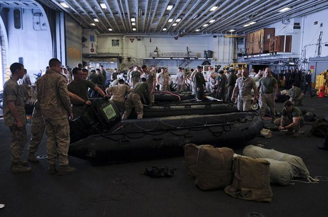 Marines assigned to the 31st Marine Expeditionary Unit prepare combat rubber raiding crafts (CRRC) in the hangar bay of the forward-deployed amphibious assault ship USS Bonhomme Richard (LHD 6). Bonhomme Richard is responding to the scene of Korean passenger ship Sewol that sank near the island of Jindo off the southwestern coast of the Republic of Korea April 16, 2014. (U.S. Navy/Mass Communication Specialist 2nd Class Adam D. Wainwright)