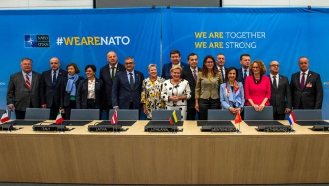 NATO member defense ministers for 16 nations, and Macedonia, stand together at the summit in Brussels after agreeing to procure land munitions together in an effort to lower costs for all of the countries. Photo courtesy of NATO