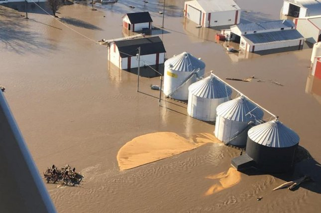 This aerial view of the flooded Kellogg family farm in western Iowa shows two burst grain bins with golden corn spilled across the ground. There is no insurance plan to cover stored crops. The newly passed disaster aid bill will include money for farmers who lost such crops. Photo courtesy of Beth Kellogg
