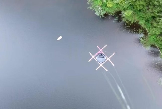 A drone carrying a cup of coffee slowly descends toward a row boat. Screenshot: Storyful