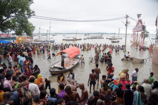 Worshipers walk outside a temple in flooded waters in Allahabad, Uttar Pradesh, India, on Sunday. Photo by EPA-EFE