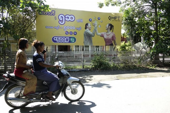 Two Rakhine women ride a motorcycle past a telecommunications advertisement poster in Sittwe, Rakhine state, Myanmar. File Photo by Nyunt Win/EPA-EFE
