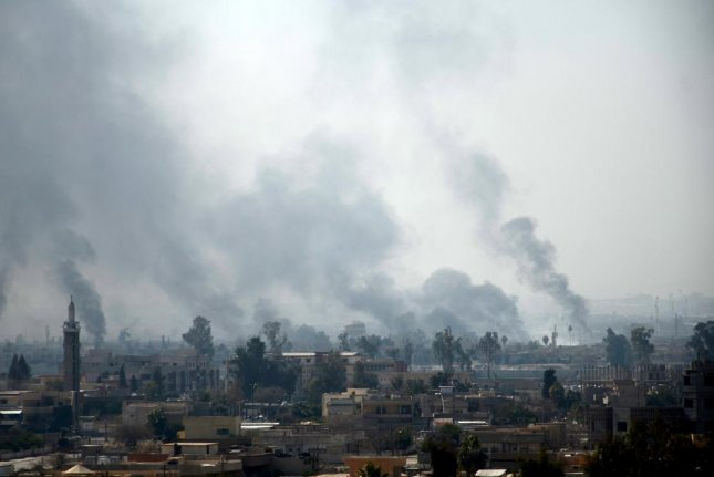 Smoke clouds rise from the western part of Mosul, Iraq on Feb. 27. The World Health Organization said 12 people, including women and children, have required medical treatment for conditions consistent with the use of chemical weapons near Mosul, which is still partially controlled by the Islamic State. Photo by STR/EPA