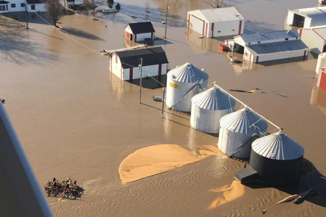 A 2019 aerial view of a flooded farm in western Iowa shows two burst grain bins with golden corn spilled across the ground. File Photo courtesy of Beth Kellogg