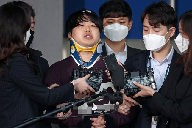Suspect Cho Ju-bin, 24, faces reporters Wednesday while being transferred to the prosecutor's office in Seoul. He is accused of operating chat rooms that shared violent and degrading sex videos he obtained through blackmail and coercion. Photo by Yonhap