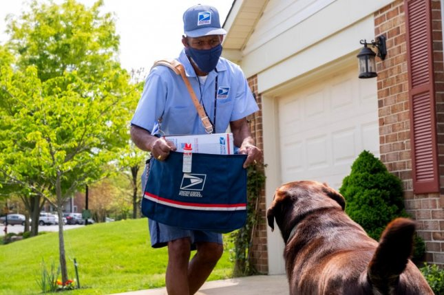 A letter carrier in Annapolis, Md., takes a protective stance against an approaching dog. Photo courtesy of USPS