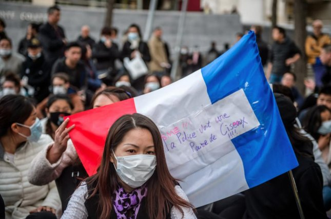 Members of France's Chinese community gather outside a police station to protest against police violence in Paris on Tuesday. The French government may fear a recent attack on a French citizen in Shanghai had retaliatory motives. Photo by Christophe Petit/EPA
