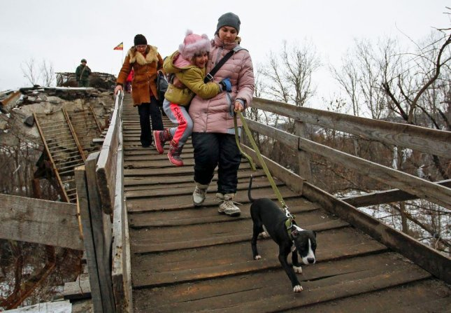 Residents in eastern Ukraine cross a damaged bridge between government-held and separatist-held territory. Officials said they are prepared to evacuate the town of Avdiivka, under siege since Friday. Photo by Alexander Ermochenko/EPA