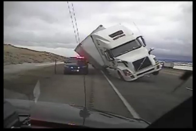 Wind blows semi truck onto unoccupied police car in Wyoming